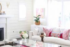 a fresh summer family room with a fireplace, a white sofa and stools, a glass table, colorful pillows and artworks