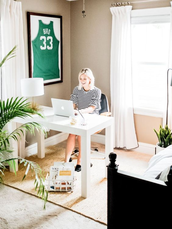 a fun bedroom with a dark carved bed, a white desk and a chair for working, potted plants and a sport top in a shadow box