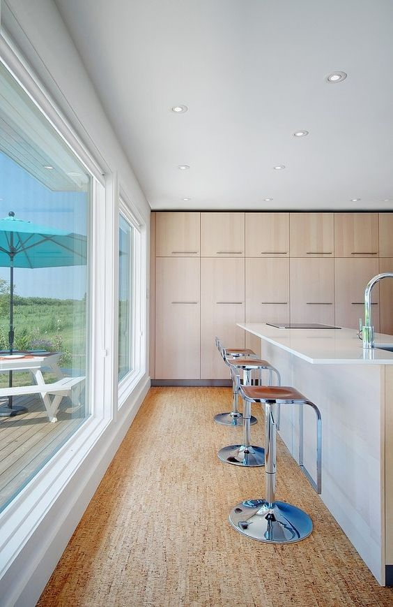 a glazed wall, a white kitchen island, tall stools placed on the cork floor that adds interest and warmth here