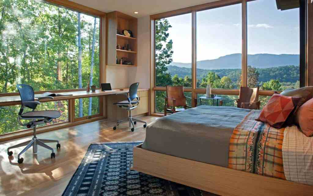 a gorgeous bedroom with a view through glass walls, a floating desk, storage units and a sitting space by the window
