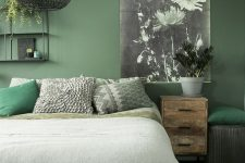 a green summer bedroom with simple furniture, a black woven pendant lamp, a floral artwork and green printed bedding