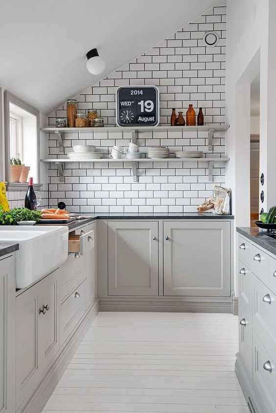 a grey Scandi attic kitchen with white subway tiles, black stone countertops, open shelves and neutral knobs is chic