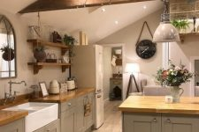 a grey farmhouse attic kitchen with butcherblock countertops, open shelves and wooden beams, a mirror and a vintage faucet
