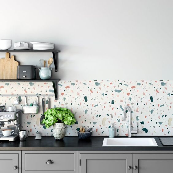 a grey kitchen with black countertops and a cheerful terrazzo backsplash plus black metal shelves is a cool idea