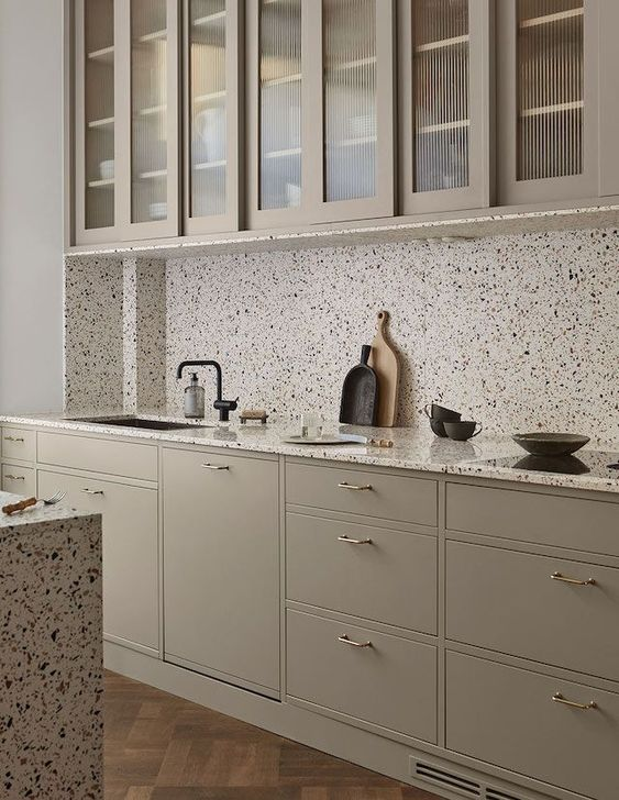 a grey kitchen with brass handles and catchy white terrazzo countertops and a backsplash plus black fixtures is chic