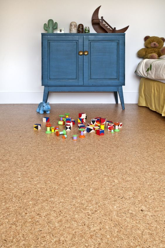 a kid's space with white walls and a cork floor, a bed and a blue cabinet, colorful toys and bold decor is a veyr cute room