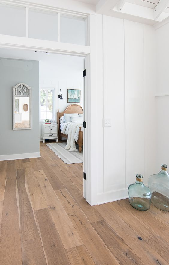 a lake space with white planked walls and bamboo flooring, a wooden bed, a blue accent wall and some pretty accessories