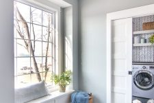 a laundry room with grey walls and a grey tile floor, a windowsill bench and a sliding door is a very cool and simple idea