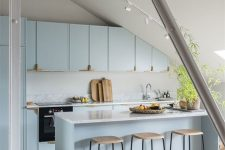 a light blue attic kitchen with sleek cabinets and a kitchen island, a skylight, a potted plant and stools is chic