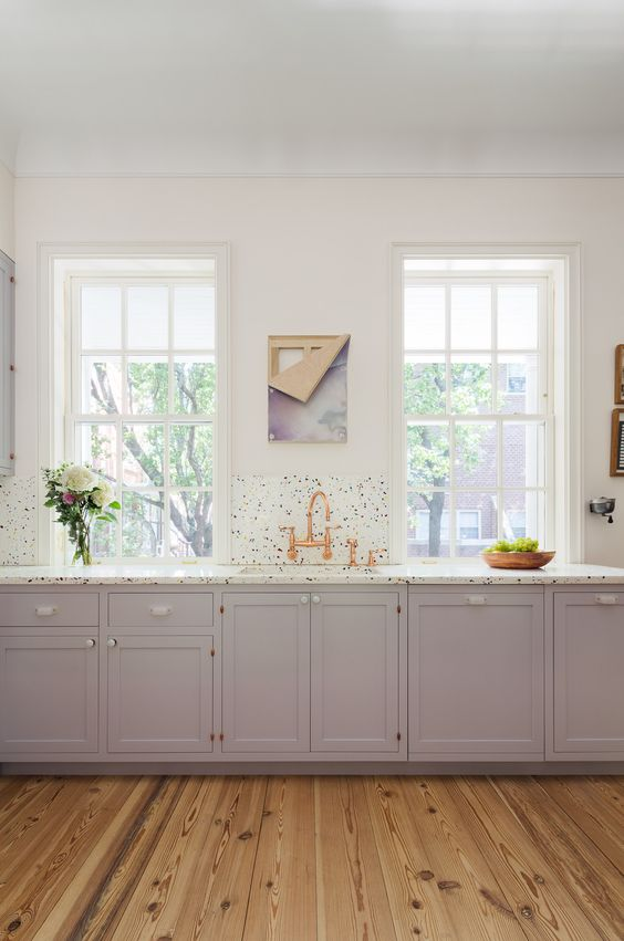 a lilac kitchen with a cheerful terrazzo backsplash and countertops plus copper fixtures is a chic space