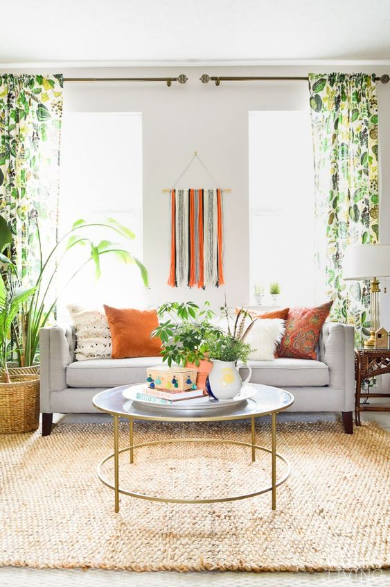 a lively summer living room with a grey sofa, bold pillows and bold printed curtains, a fringe decoration and lot sof plants