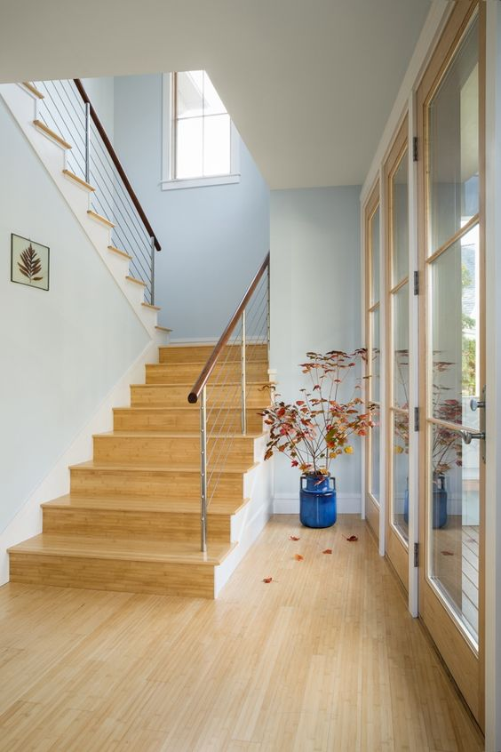a lovely and welcoming entrance with bamboo floors and a staircase clad with the same bamboo to make the space more cohesive
