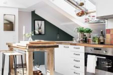 a lovely attic kitchen with white cabinets, a tall wooden kitchen island and table, a lovely woven lamp and artworks
