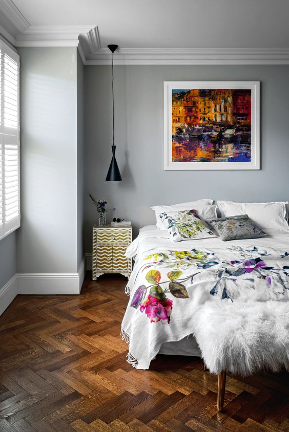 a lovely bedroom with grey walls, a dark stained parquet floor, chic furniture with floral bedding and a bold watercolor artwork