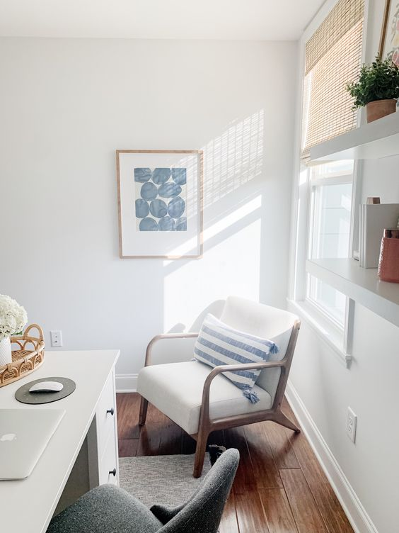 a lovely coastal home office in neutrals, with a white desk, a comfy chair, touches of blue and shades on the window