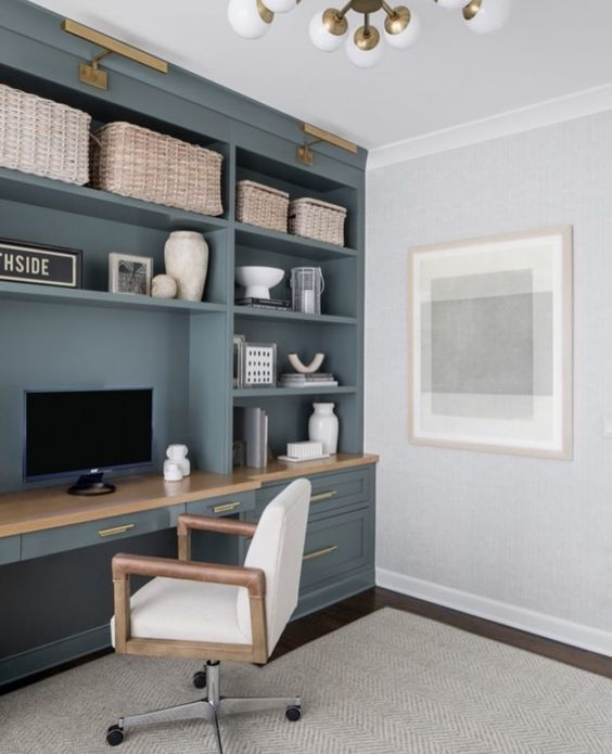 a lovely coastal home office with a blue built-in storage unit with a desk, a white chair, some baskets for storage