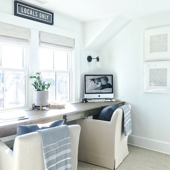 a lovely coastal shared home office with a shared desk, two chairs, blue textiles and shades on the windows