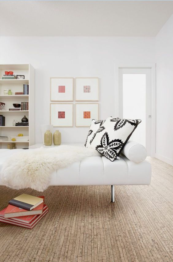 a lovely contemporary space with white walls and a cork floor, white and creamy furniture and rugs, printed pillows and a mini gallery wall