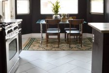 a lovely eat-in kitchen with a tile floor and black walls, dark cabinetry, lovely leather chairs and a metal dining table