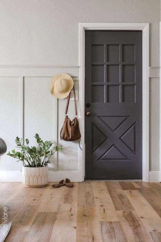 a lovely entryway with a grey door, a vinyl floor, a potted plant, a hat and some stuff looks chic and elegant