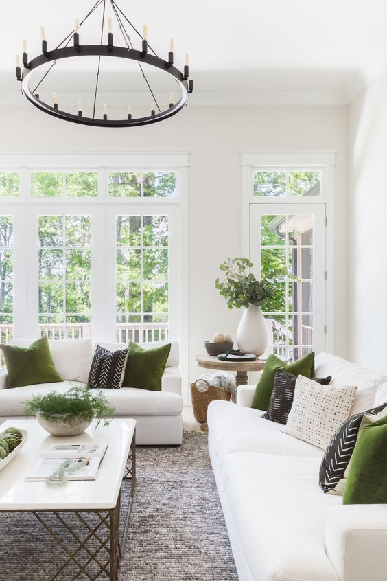 a lovely farmhouse living room with a glazed wall, white sofas, printed and green pillows, a coffee table and a chandelier