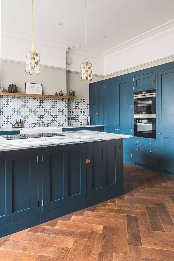 a lovely kitchen with a rich stained parquet floor, deep blue cabinets and a kitchen island and lovely mosaic tiles
