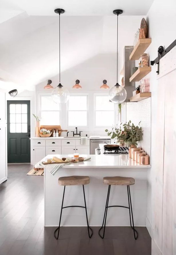 a lovely kitchen with white cabinetry and black knobs, floating shelves and a metal hood, tall stools and pendant lamps