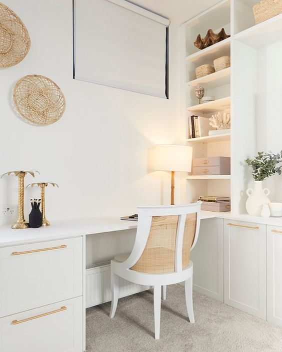 a lovely neutral coastal home office with a built-in storage unit, a built-in desk, a rattan chair, baskets and touches of gold