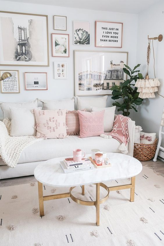 a lovely neutral living room with a white sofa, neutral and pink pillows, a large gallery wall, a marble table and a tassel pendant lamp