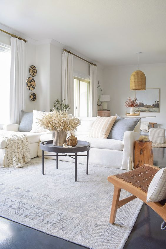 a lovely neutral summer living room with a white sectional, a leather woven chair, a couple of side tables and decorative plates
