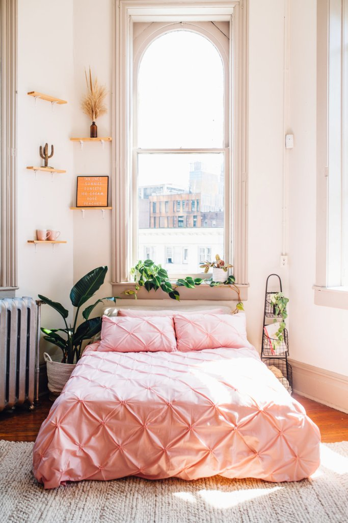 a lovely summer bedroom with tall windows, mini shelves with various decor, a bed with pink bedding and lots of plants