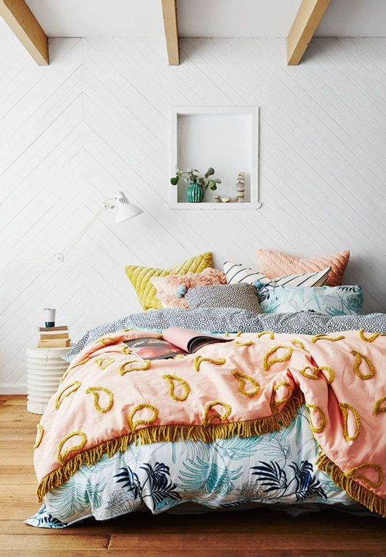 a lovely summer bedroom with wooden beams on the ceiling, a bed with pretty pastel bedding, a niche for decor and a white lamp