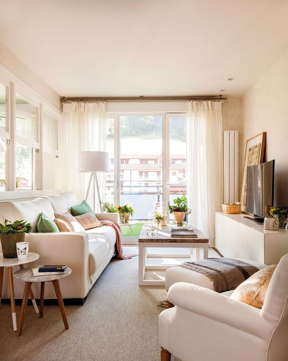 a lovely summer living room with creamy furniture, green and blush accents, potted greenery and a lovely view from the balcony