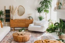 a lovely summer living room with white furniture, warm earthy textiles, potted plants, a fireplace and a wooden coffee table