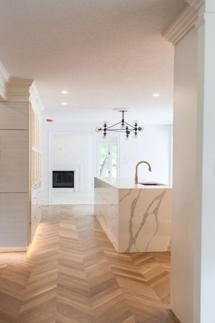 a luxurious minimalist kitchen done with white cabinetry, a white marble kitchen island and a lovely parquet floor plus a chic chandelier
