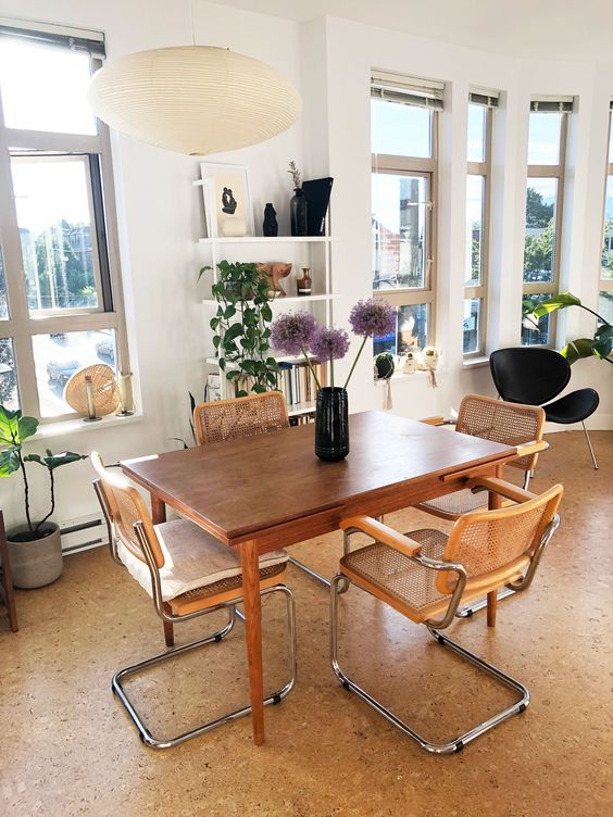 a mid-century modern dining room with a row of windows, a stained table and rattan chairs, potted plants and decor