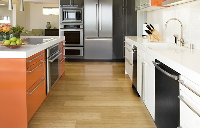 a mid-century modern kitchen with bamboo flooring, an orange kitchen island and metal items and touches is cool