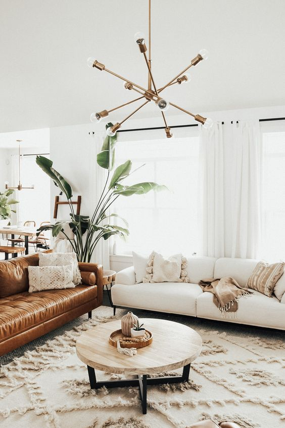 a mid-century modern living room with a white sofa, a low coffee table, a leather sofa, a boho rug and a modern chandelier