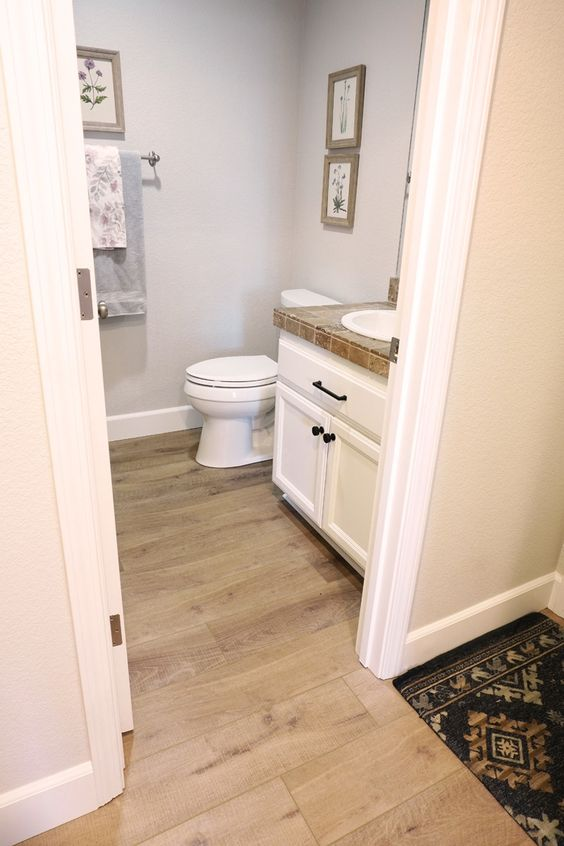 a mini bathroom with grey walls and a vinyl floor, white furniture and appliances and some artworks is a very cool and chic idea