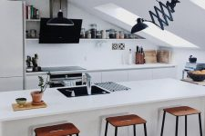 a minimalist attic kitchen with sleek cabinetry, tall stools, skylights, black fixtures looks very stylish and bold