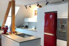 a minimalist attic kitchen with sleek white cabinetry, a bold red fridge, wooden beams and lights over the spac