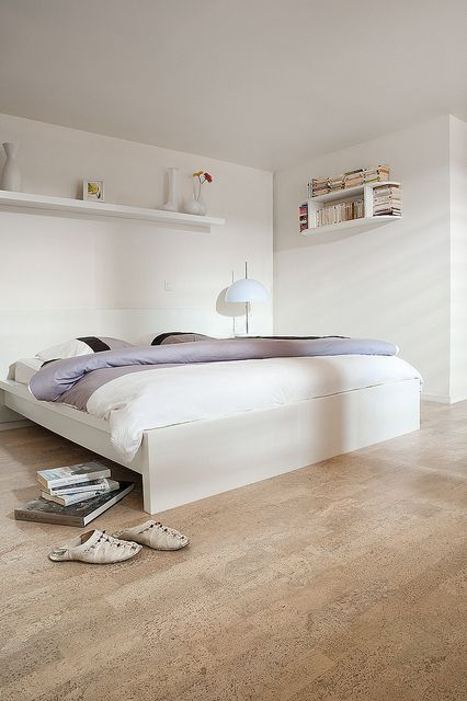 a minimalist bedroom with white walls, a cork floor, white shelves and pastel bedding is a welcoming and veyr airy room