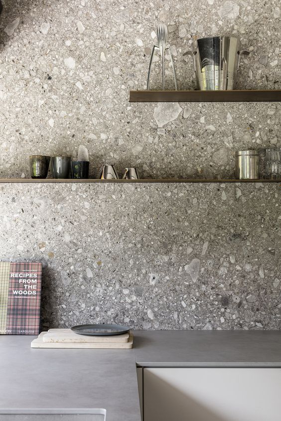 a minimalist grey kitchen with concrete countertops and a grey terrazzo backsplash, with floating shelves is a chic space