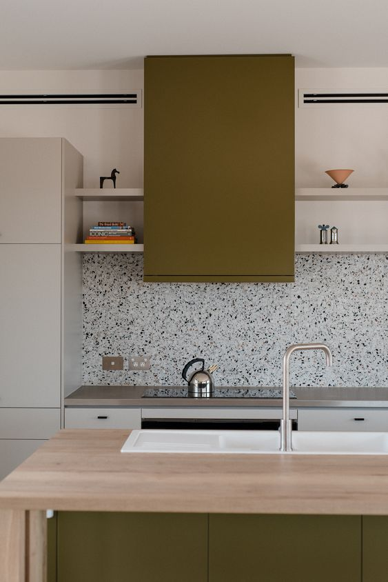 a minimalist kitchen done in grey and grass green, with grey countertops and a cool terrazzo backsplash in black and white