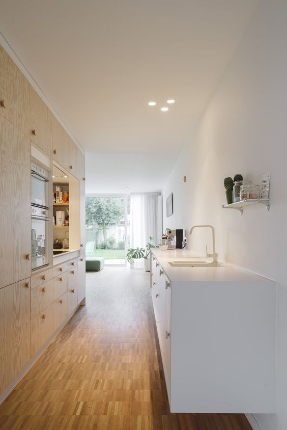 a minimalist kitchen with a bamboo floor, plywood cabinetry, a white kitchen island and built-in lights looks elegant and chic