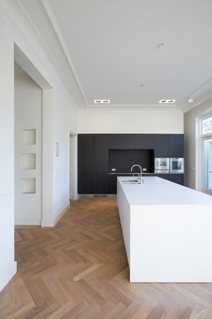 a minimalist kitchen with black cabinetry, a white kitchen island and a parquet floor plus built-in lights is chic