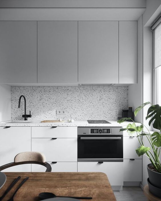 a minimalist light grey kitchen with black handles and a white and black terrazzo backsplash and countertops is wow