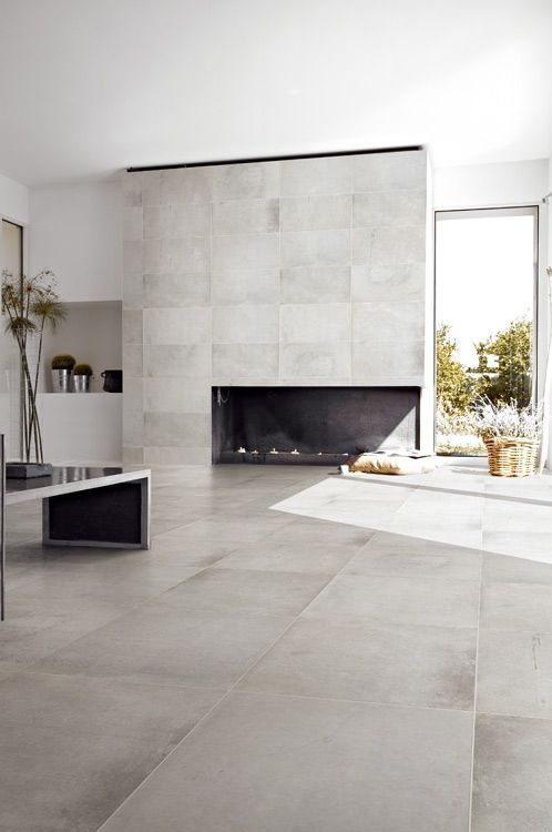 a minimalist living room clad with the same tiles - on the floor and fireplace, a bench, potted greenery and baskets for storage