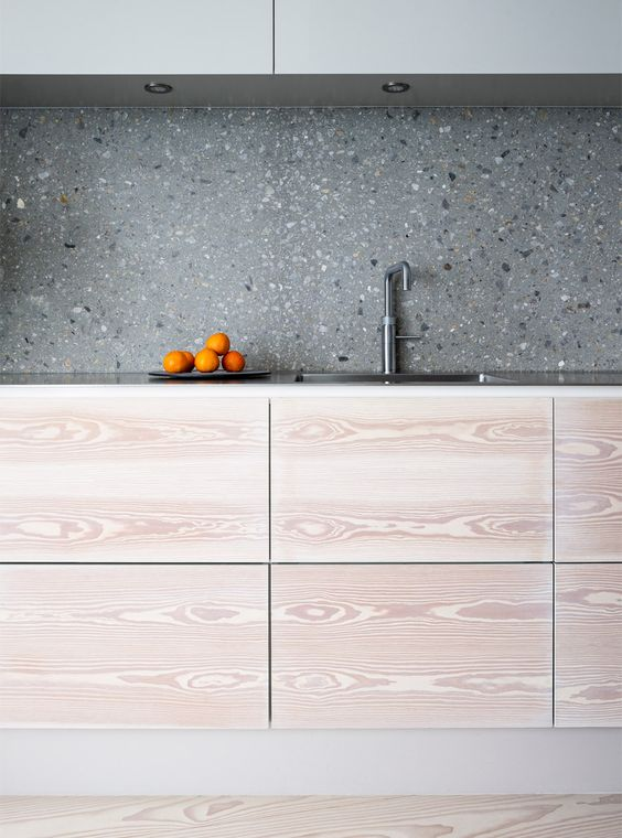 a minimalist two-tone kitchen with sleek cabinetry and a grey terrazzo backsplash plus metal countertops looks chic