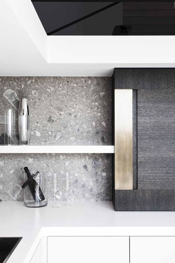 a minimalist white kitchen with a grey terrazzo backsplash, a black cabinet with metallic touches is a bold and cool idea